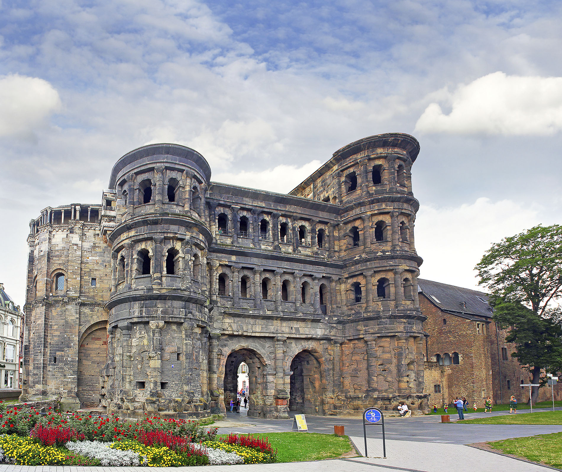 The impressive Roman gate of Porta Nigra amongs tourists and fragrant flower beds Trier, Germany