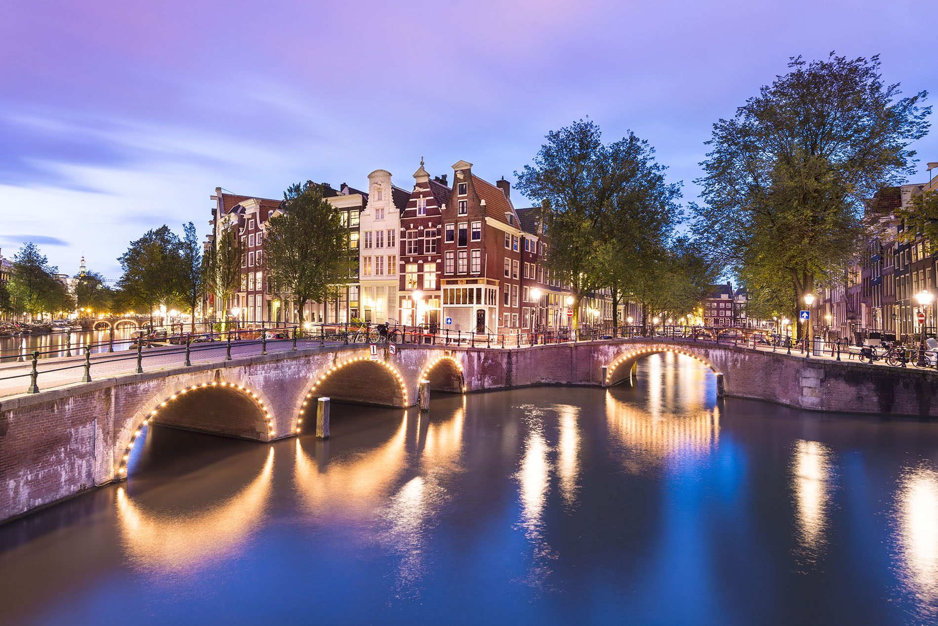 Bridges and canal houses line the canal in Amsterdam at twilight, Holland.
