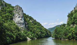 a body of water surrounded by trees with Rock sculpture of Decebalus in the background