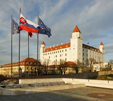 a large white building with Bratislava Castle in the background