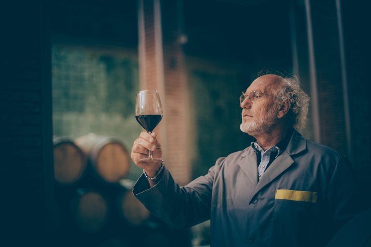 Old man looking at wine glass