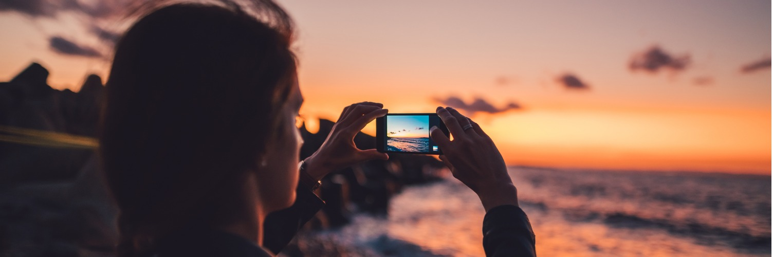 Taking pictures by the sea at sunset